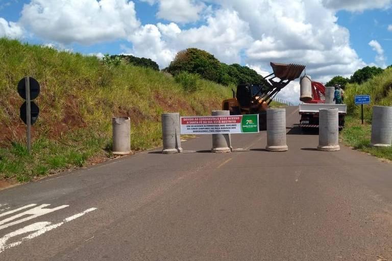 Blocos de concreto enfileirados em estrada; ao fundo, um trator pega uma peça