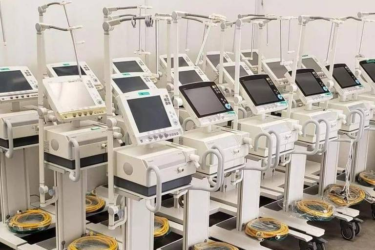 Ventiladores pulmonares anunciados em site; venda dos aparelhos recondicionados é controlada por lei; foto mostra uma série de aparelhos hospitalares reunidos lado a lado, são 18 quase idênticos, brancos, com uma telinha, e com fios amarelos enrolados sobre sua base, que tem rodas