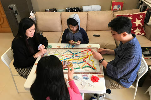 Derek Au, a 46-year-old manager at a non-profit organization, plays a board game with his wife and children at their home following an outbreak of the novel coronavirus, in Hong Kong, China February 24, 2020. Picture taken February 24, 2020. REUTERS/Aleksander Solum ORG XMIT: HFSPEK01