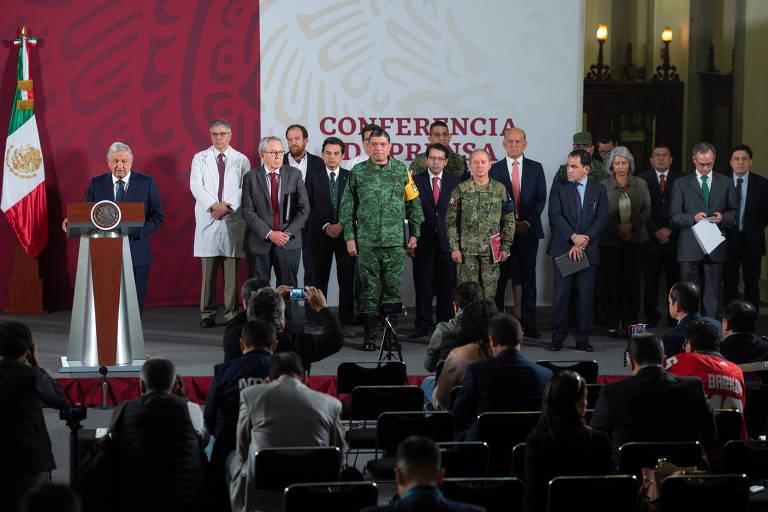 O presidente mexicano, Andrés Manuel López Obrador, anuncia novas medidas de distanciamento social contra o coronavírus enquanto seus ministros ficam próximos um do outro no palco
