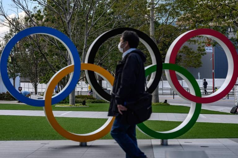 Homem com máscara contra o coronavírus passa pelos aros olímpicos em Tóquio; Jogos foram adiados para o ano que vem, ainda sem data para acontecer