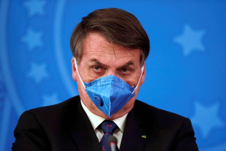 Jair Bolsonaro, de máscara, durante coletiva de imprensa