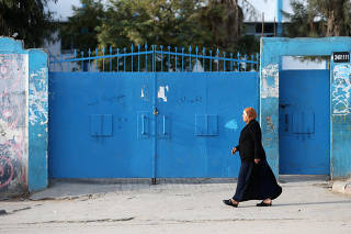 A Palestinian woman walks past a United Nations-run school closed as a precaution measure against coronavirus, in Khan Younis in the southern Gaza Strip