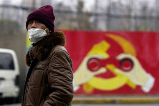 FILE PHOTO: A man wears a mask as he walks past a mural showing a modified image of the Chinese Communist Party emblem in Shanghai