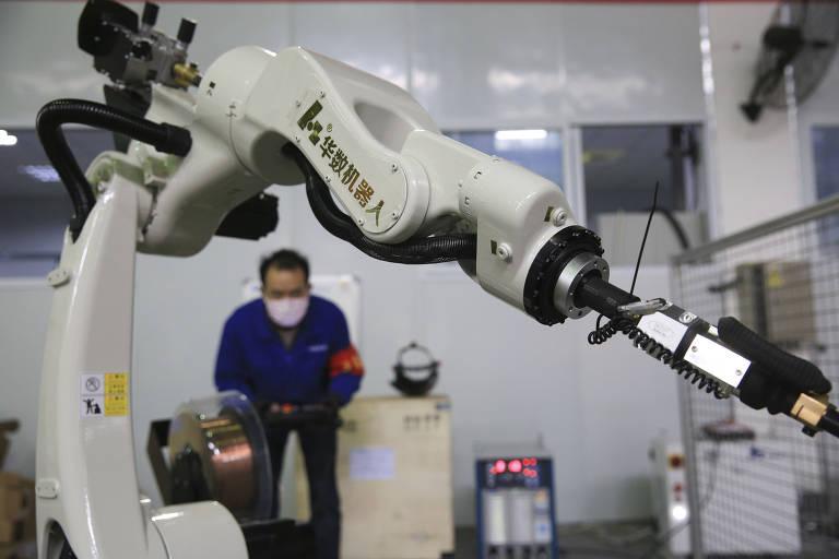 Empregado em fábrica de robôs em Beibei, no sudoeste da China, testa equipamento; companhias retomaram produção de autômatos em meio à crise do novo coronavírus; na foto, vemos um homem de azul, com máscara, ao fundo; em primeiro plano, uma espécie de enorme braço mecânico branco, com uma ponteira de metal