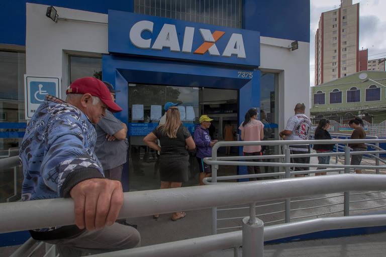 Um homem em uma fila da Caixa Econômica Federal; ele está de máscara, boné vermelho e segura no corrimão