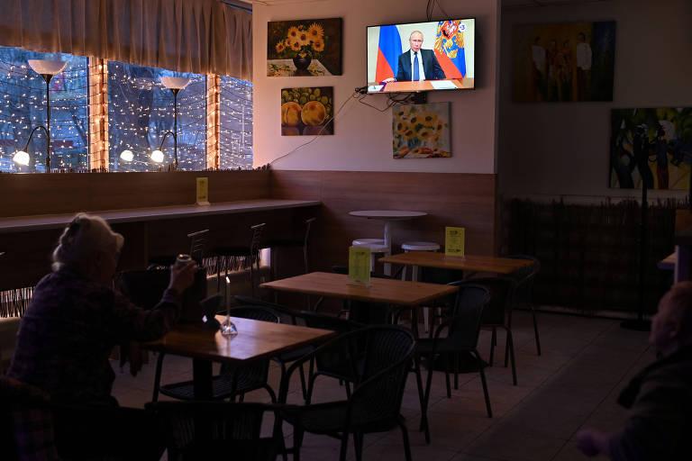 Em café em Omsk, pessoa assiste ao pronunciamento do presidente Vladimir Putin sobre coronavírus