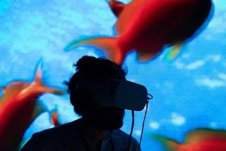 Silhueta de pessoas com óculos de realidade virtual à frente de uma tela com imagem de peixes