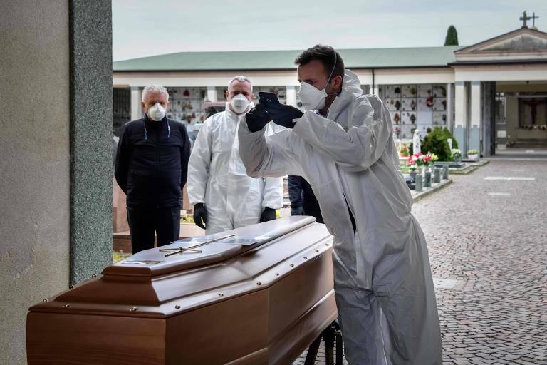 Funcionário de cemitério tira foto de caixão para familiares que não puderam ir a enterro de pessoa que morreu devido à Covid-19 em Bergamo, na Itália
