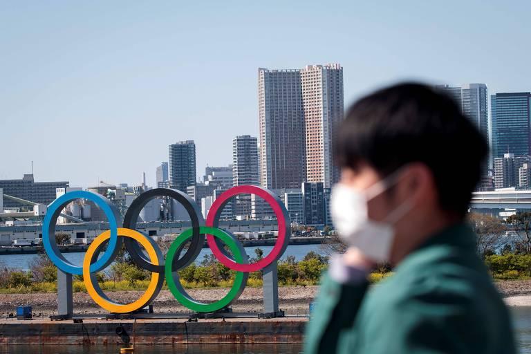 Homem caminha falando ao celular e utilizando uma máscara de proteção próximo ao monumento dos anéis olímpicos de Tóquio, no Japão