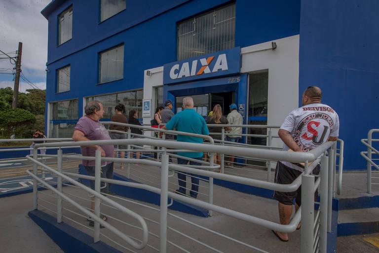 Idosos fazem fila em frente a uma agência da Caixa, em São Paulo, para sacar o INSS