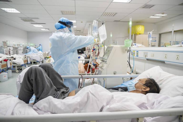 Paciente recebe hemodiálise em centro especializado de nefrologia no hospital Hankou, em Wuhan, foco inicial da pandemia de Covid-19; na foto vemos em primeiro plano um paciente com máscara em uma cama hospitalar, com as pernas dobradas, e um profissional de saúde que manipula o equipamento de diálise, à esquerda no quadro, logo ao lado da cama