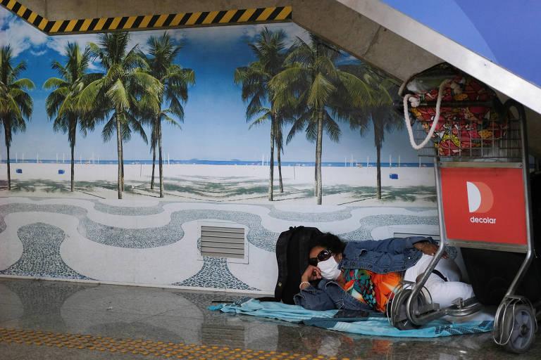 Mulher deitada no chão, ao lado de suas malas, com máscara cirúrgica. Na parede, há uma foto grande de praia. A foto dá a ilusão de que ela está na praia