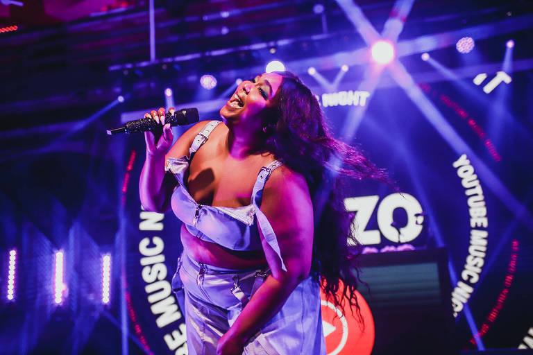 Mulher negra e gorda canta usando roupas lilás