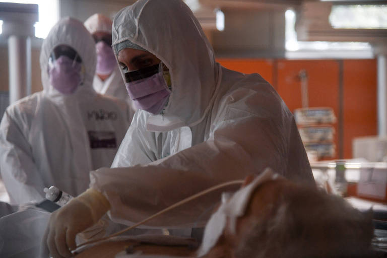 Médico atende paciente usando trajes para evitar contágio