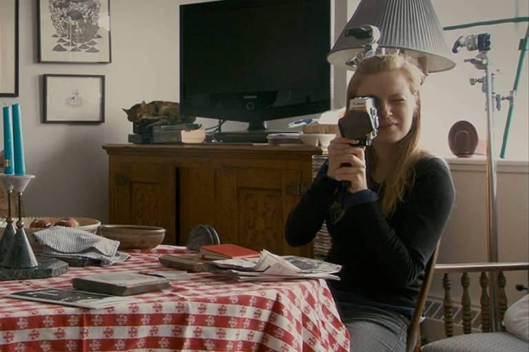 menina loira numa sala de estar aponta uma câmera de filmagem para o fotógrafo