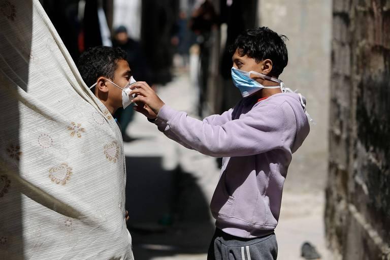 Crianças palestinas brincam com máscaras em campo de refugiados em Gaza