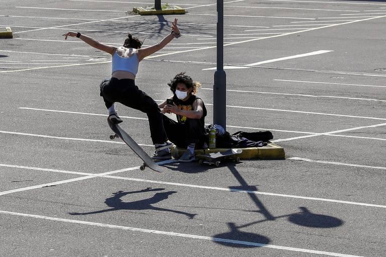 Adolescente faz manobra de skate enqanto outro, sentado e com máscara cirúrgica observa
