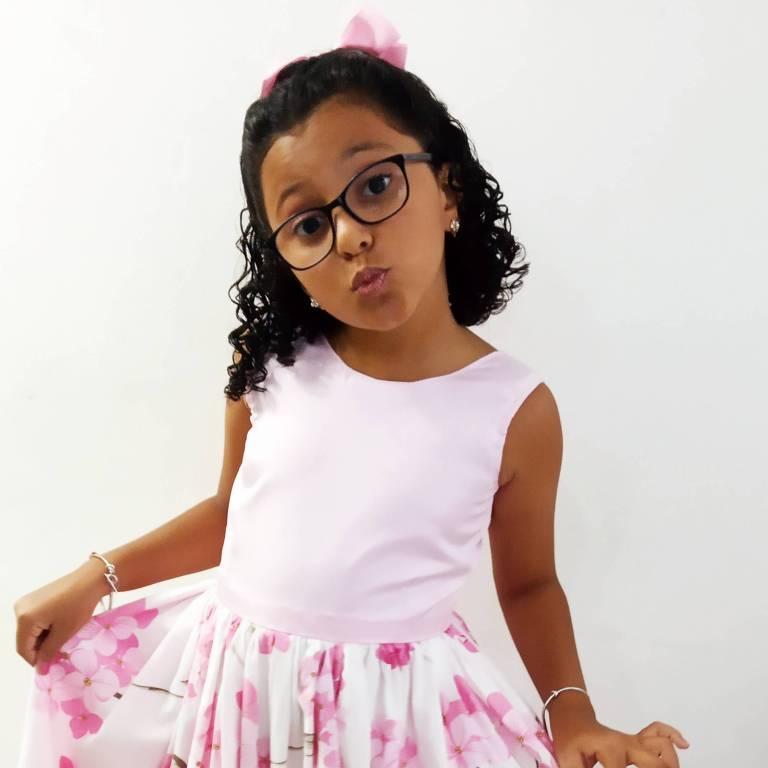 Heloísa está de vestido branco com flores rosas e segura a barra da saia do vestido com as mãos