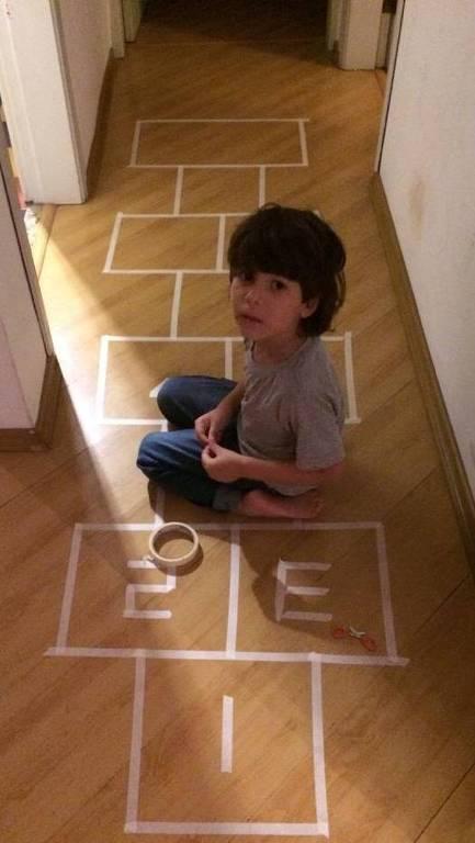 Pedro Pliger, 5 anos, está sentado no meio do corredor de sua casa. Ele está desenhando com fita crepe uma amarelinha para brincar em casa