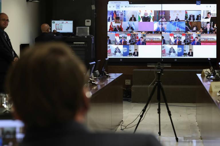 O presidente Jair Bolsonaro (de costas) observa tela com outros líderes do G20 durante videoconferência