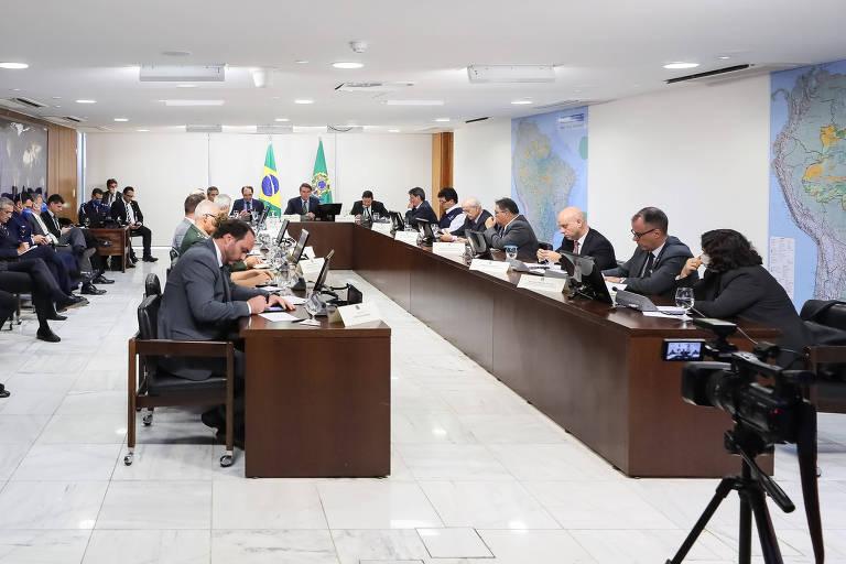 Sala com duas longas mesas de reunião ocupada por pessoas