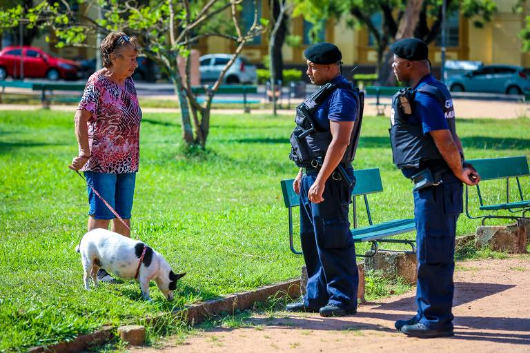 Guardas abordam mulher que passeava com cão no parque Farroupilha; até 15 de abril, idosos só podem sair de casa para fins essenciais; ela está de camiseta rosada e bermuda jeans, levando um cachorrinho médio, branco e preto; ela está parada sobre a grama, junto a bancos, e dois guardas conversam com ela