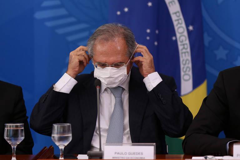 O ministro da Economia, Paulo Guedes, durante anúncio de medidas do governo pra conter a epidemia de Coronavírus, no Palácio do Planalto. Ele ajeita a máscara no rosto.
