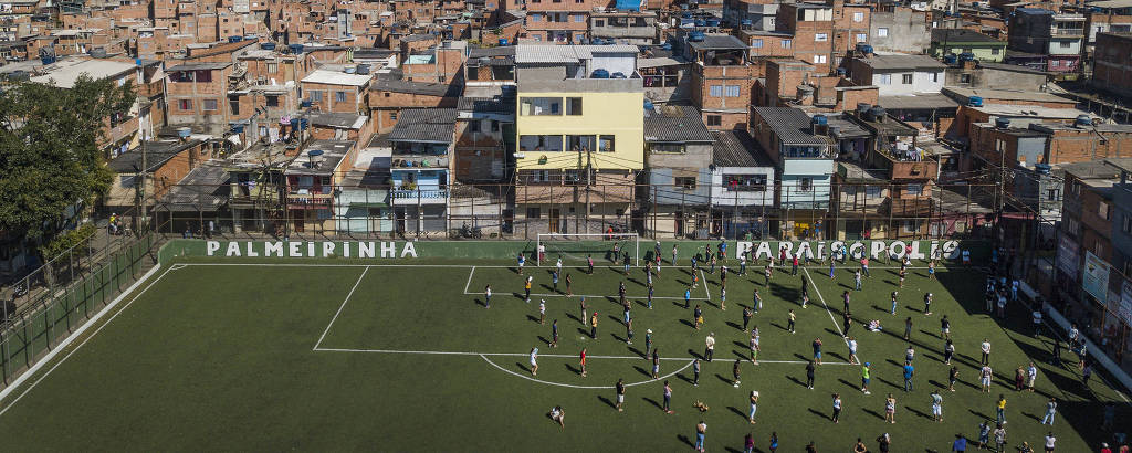 Mantendo espaço entre si, líderes de ruas da favela Paraisópolis se reúnem  no campo de futebol da favela para receber doação de sabão em barra e álcool em gel que serão repassados para os moradores