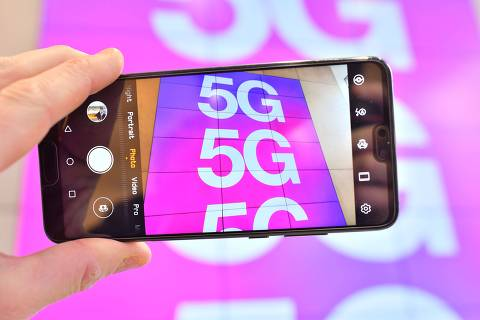 (FILES) In this file photo taken on January 28, 2020 A person poses holding a mobile telephone the camera showing a sign advertising 5G mobile telecommunication in a shop in London on January 28, 2020. - British telecoms giant Vodafone said on February 5, 2020 that it would cost 200 million euros ($221 million) over five years to remove Chinese group Huawei's equipment from core 5G European activities. (Photo by Justin TALLIS / AFP)