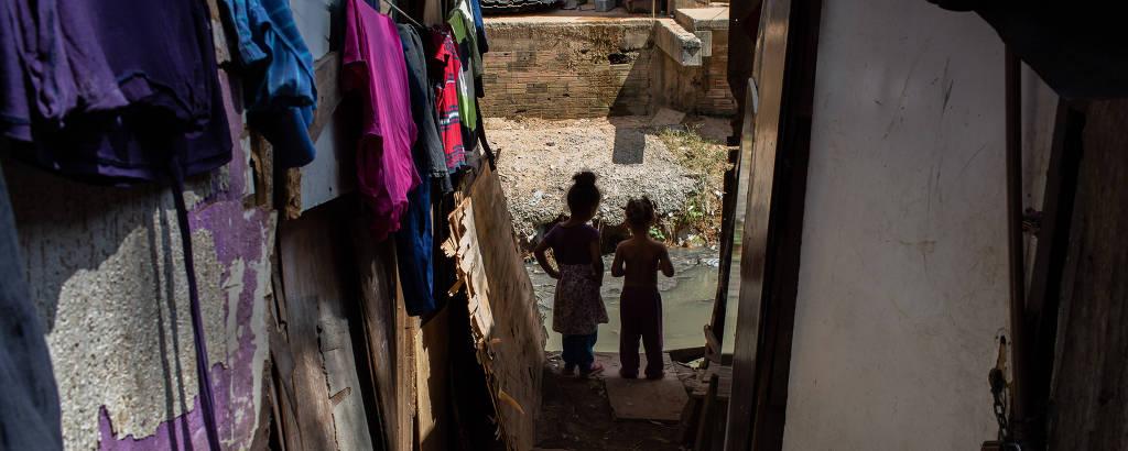 Favela Nazzali localizada na Vila Nova Cachoeirinha, na zona norte de São Paulo; foto mostra duas crianças em contra-luz, de forma que não se veem seus rostos, na parte de baixo de um beco em descida, com roupas penduradas do lado esquerdo