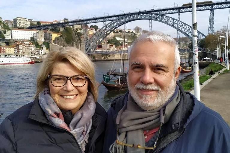 Luiz Villela e sua mulher, Jaqueline, em Portugal; ambos contraíram Covid-19, mas ela teve alta, enquanto ele morreu por no último dia 20, em Petrópolis; casal aparece com roupas de frio, sorridentes, tendo ao fundo um rio e uma ponte metálica