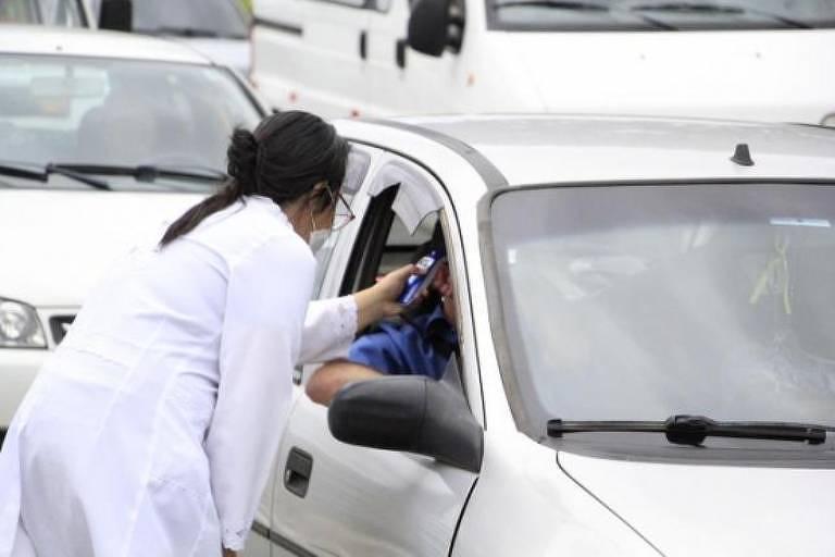 Servidora da prefeitura afere temperatura de em passageiro de veículo em barreira sanitária em Itatiba (SP)