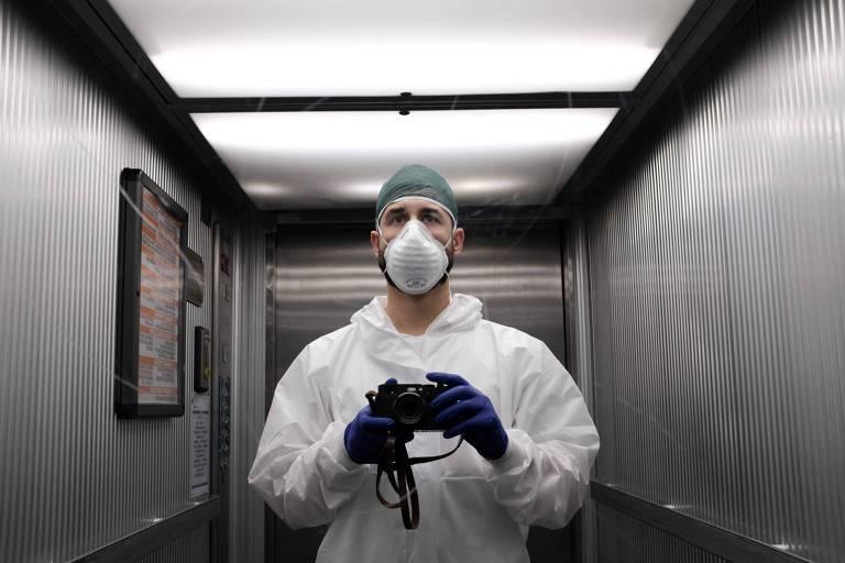 enfermeito com equipamento de proteção, incluindo máscara, tira selfie em espelho de elevador