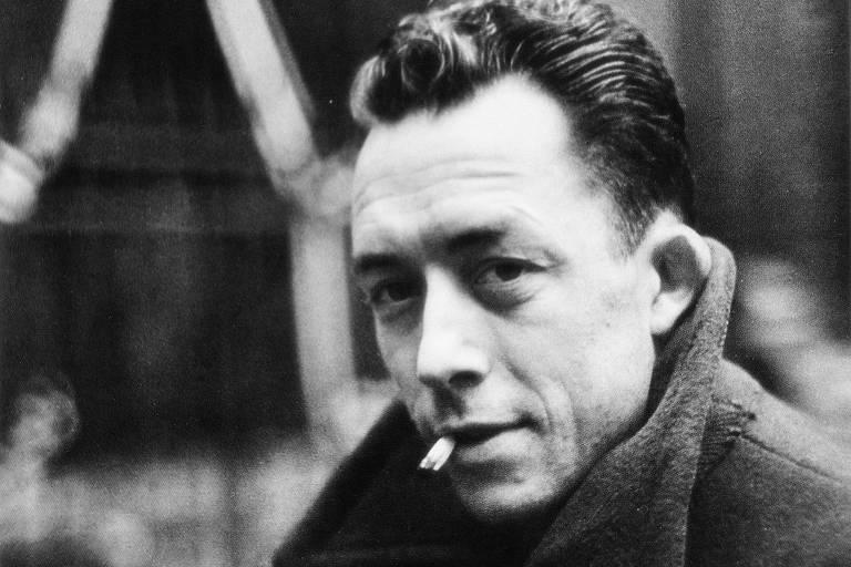 homem branco com casaco de gola olhando para o lado, sorrindo e fumando um cigarro