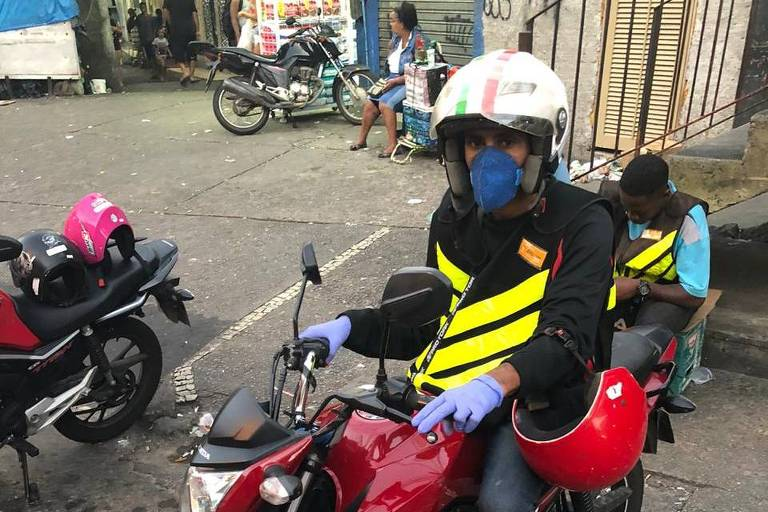 Mototaxista em cima de moto vermelha, com máscara cirúrgica azul, luvas azuis, capacete, colete preto com faixas amarelas