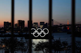 The Olympic rings are pictured at dusk through a steel fence, at the waterfront area of the Odaiba Marine Park, after the postponing of the Olympic Games Tokyo 2020, due to the outbreak of coronavirus disease (COVID 19), in Tokyo