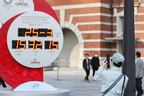 (200325) -- TOKYO, March 25, 2020 (Xinhua) -- A pedestrain takes photos of a countdown clock no longer showing the days left until the opening ceremony of Tokyo Olympic Games in Tokyo, Japan on March 25, 2020. Organizers of the Tokyo Olympic Games (Tokyo 2020) will set up task force to resolve the issues arising after the postponement of the Olympic and Paralympic Games. (Xinhua/Du Xiaoyi)