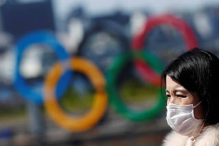 People wearing protective face masks due to the outbreak of coronavirus disease (COVID-19) walk in front of the Giant Olympic rings at the waterfront area at Odaiba Marine Park in Tokyo