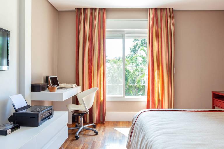Quarto com escritório no canto, com cadeira de rodinhas e mesa de madeira branca; o quarto tem cortinhas coloridas em tons de laranja e amarelo