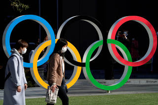 Women wearing protective face masks following an outbreak of the coronavirus disease walk past the Olympic rings in Tokyo