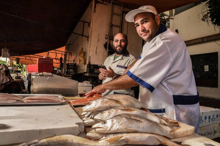 Dois homens em uma banca de peixes em uma feira