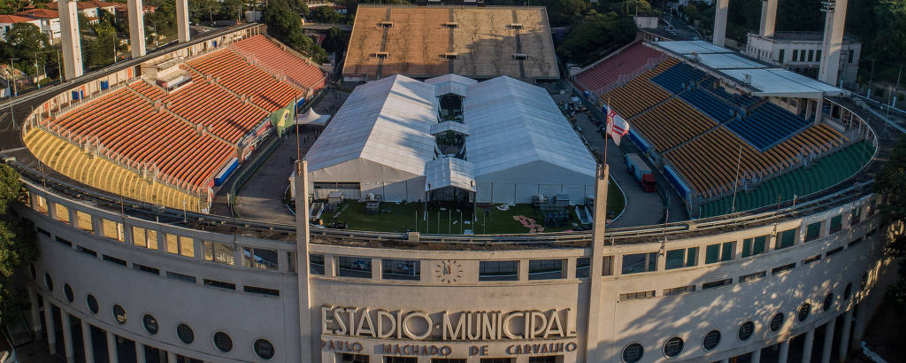 Obras de instalação do Hospital Municipal de Campanha de Combate ao Coronavírus no estádio do Pacaembu; na foto temos uma vista aérea do estádio, mostrando uma parte do seu entorno; ocupando o gramado, uma estrutura composta de dois galpões brancos com cobertura branca