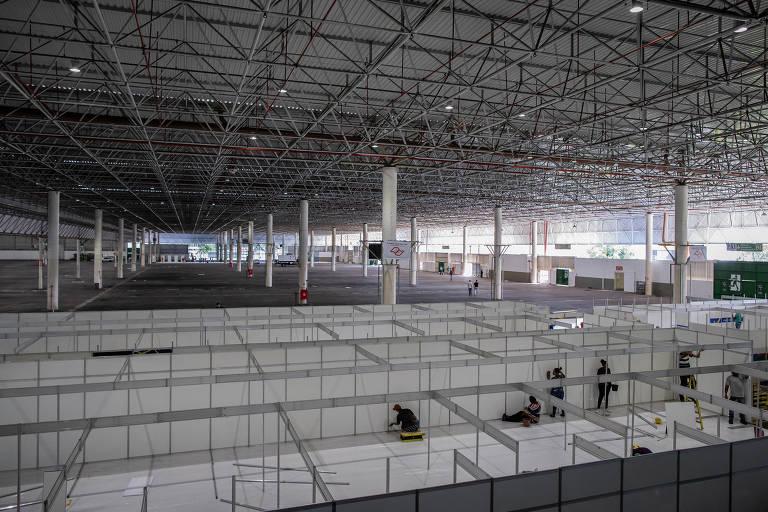 Obras de instalação de 300 leitos provisórios no Anhembi para tratamento de pacientes com coronavírus; na foto, temos uma visão geral do enorme complexo, com sua característica estrutura metálica; o chão está sendo dividido com baias, como de escritório, para formar os recintos para os leitos