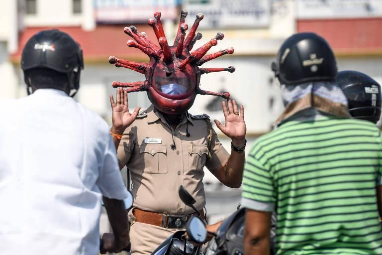 Policial usa máscara com formato do coronavírus na Índia; veja fotos de hoje