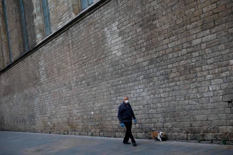 Homem caminha com cachorro em rua vazia de Barcelona