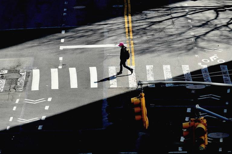 Pessoa atravessa rua vazia em Nova York em meio à pandemia de coronavírus