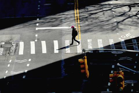 TOPSHOT - A person crosses the street on March 27, 2020 in New York City. - The US now has more COVID-19 infections than any other country, and a record number of newly unemployed people, as the coronavirus crisis deepens around the world. (Photo by Angela Weiss / AFP)