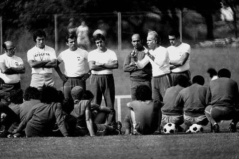 Técnico na Copa de 1970, Zagallo, com os dedos em riste, orienta os jogadores em treino. Ao centro, de braços cruzados, observa o então preparador físico Carlos Alberto Parreira