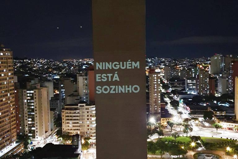 """Mensagem projetada na lateral de um prédio diz """"Ninguém está sozinho"""""""